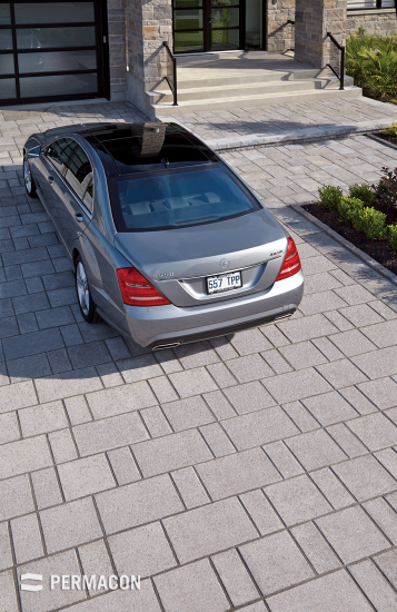 Linear and monochromatic pavers on this driveway add a contemporary finishing touch to the home